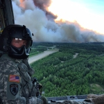 The Alaska Army National Guard supported fire suppression efforts in June 2015 in and near Willow, Alaska. UH-60 Black Hawks from the 1-207th Aviation Regiment flew multiple missions, dipping their orange water buckets into waters east of Willow Lake and dropping thousands of gallons of water over the east side of the fire, about five miles north of Willow Airport. Sgt. Sonny Cooper, a crew chief for the 1st Battalion, 207th Aviation Regiment, flew on a crew during firefighting efforts, and operated the water bucket during missions. (Photo courtesy of Sgt. Kevan Katkus)
